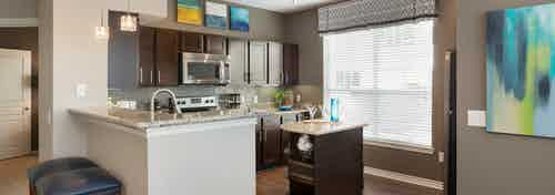 Interior of kitchen at AMLI Memorial Heights with stainless steel appliances and granite countertops and dark wood cabinets