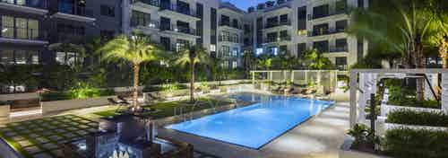 AMLI Midtown Miami courtyard pool lit up at night with arching water streams surrounded by cabanas and lush landscape