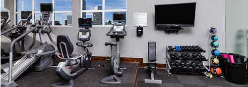 Interior view of a fitness center at AMLI Park Ave apartments with free weights and a television and various cardio machines