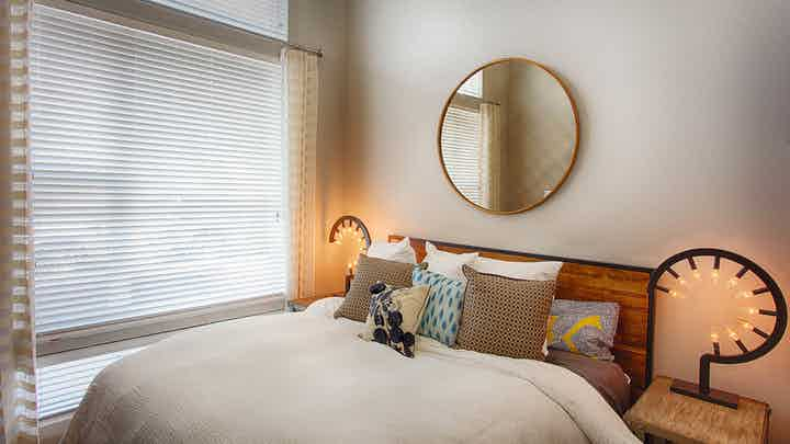 A bedroom at AMLI Denargo Market apartments featuring a bed with a wooden head board and a circular mirror and large window