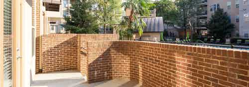 Exterior view of AMLI Lindbergh apartment community patio of with a brick wall overlooking the pool on a sunny day