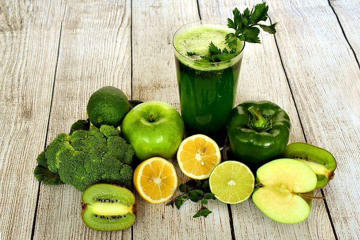A glass full of green juice, surrounded by lemons, limes, an apple, some broccoli and a green pepper