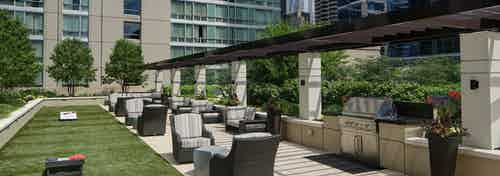 Rooftop grill area and garden at AMLI River North apartment community with surrounding outdoor seating and bright foliage