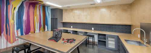 DIY maker space at AMLI Lenox with colorful painted wall and tools and sink as well as work areas for residents to create