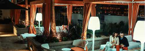 Nighttime view of AMLI Lex on Orange pool deck personal curtained cabanas with comfortable seating, patio lamps and a couple