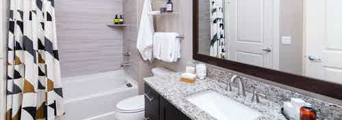 Interior of AMLI Littleton Village apartment bathroom with granite countertops, soaking tub and tile surround and soap holder