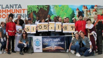 FAMLI volunteers showing total raised for Atlanta Food Bank in 2018