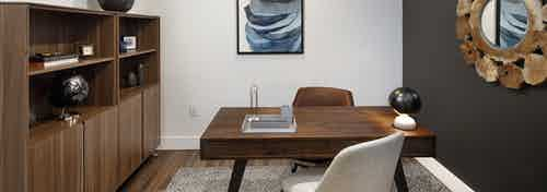 Interior of AMLI Marina Del Rey apartment office space with area rug, wood desk and two chairs and wall unit with storage