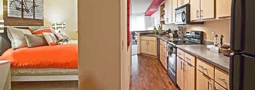 Interior entrance view of an AMLI 535 apartment where a wall divides a bedroom on the left and a kitchen on the right