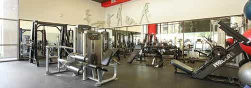 Interior of fitness center with workout equipment, free weights and surrounding mirrors at AMLI Warner Center apartments