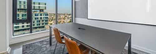 Conference room at AMLI Arc apartment building with table and two brown chairs facing a white board and wall of windows