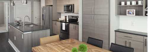 A kitchen at AMLI Riverfront Green apartment and view of dining table and kitchen island with closets in the background