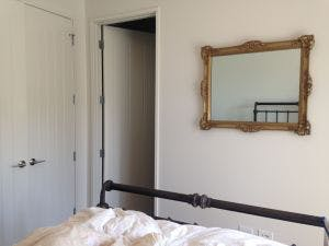 After: The mirror was replaced with a piece of art that brought color and texture into the bedroom.