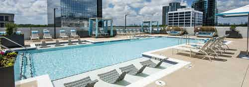AMLI Lenox rooftop pool area on a sunny day with crystal blue water and lounge chairs and cabanas surrounding pool