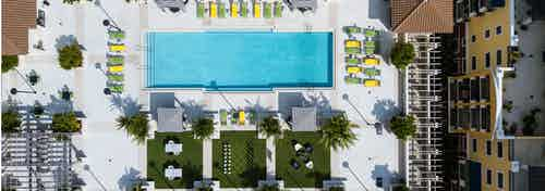 Aerial Rooftop view of the AMLI Dadeland Pool with black and white cabanas, outdoor games, green and yellow lounge chairs