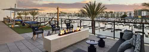 Dusk view of lounge deck with outdoor fireplace, oversized hammocks overlooking the marina at AMLI Marina Del Rey apartments