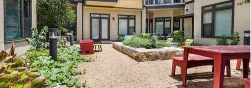 Exterior view of AMLI 5350 courtyard garden with raised red table with benches and surrounding vibrant green plants