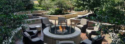 Rooftop firepit at AMLI River North with surrounding green folliage and wicker chairs centered around a firepit with a flame