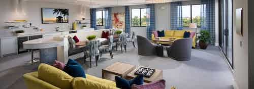 Rooftop view in the AMLI 8800 Resident Lounge seating area yellow accent furniture, TV on wall and entertaining kitchen