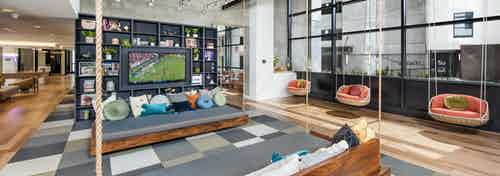 Interior view of AMLI Lenox clubhouse with three swings and seating with lots of colorful pillows and a flat screen TV