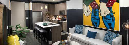 AMLI 8800 apartment living area with white sofa and artwork with blue shoes, toss pillows and a peek into the kitchen