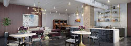 AMLI Quadrangle resident lounge with various seating and dark floors with kitchen area and hanging modern light fixtures