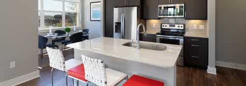 AMLI on Aldrich kitchen with white and red barstools at a quartz island with windows and dark wood cabinetry in background