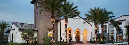 Exterior dusk rendering of AMLI Spanish HIlls apartment building's brick facade with arched entrance to office and palm trees
