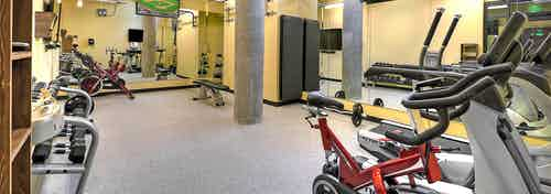 Interior of the fitness center at AMLI South Lake Union with treadmills cycle bikes free weights and fitness on demand