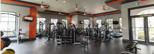 Interior of fitness center at AMLI Toscana Place with high-endurance equipment and colorful walls, Tvs and ceiling fans