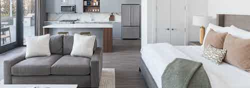 AMLI Fountain Place studio apartment with large white bed and grey couch with white coffee table and grey island kitchen