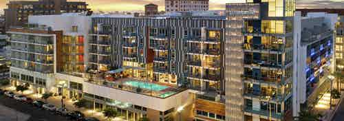 Aerial dusk exterior view of AMLI Park Broadway apartment building with lit rooftop pool and tree lined street below