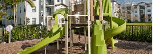 Outdoor green children's playground at AMLI Doral features stairs for climbing, two slides and all set on rubber floor