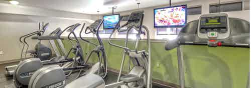 Interior of the fitness center at AMLI 535 with cardio equipment TV and vibrant walls