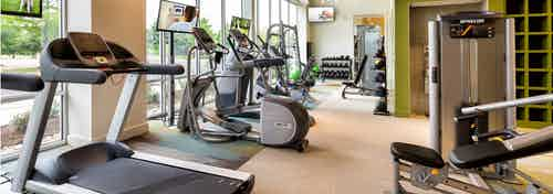 Close up view of treadmill and cardio machines in the AMLI at Mueller fitness center with beige flooring and large windows