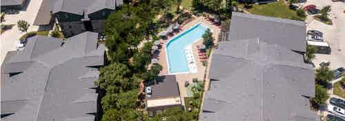 Daytime aerial view of AMLI Covered Bridge community pool with red lounge chairs and grey umbrellas for shade
