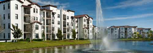 Daytime Exterior view of AMLI Doral apartment buildings surrounding a lake with a water fountain in the center
