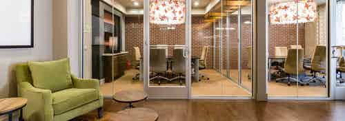 Interior view of AMLI RidgeGate conference rooms equipped with large tables and chairs, ornate chandelier and faux brick wall