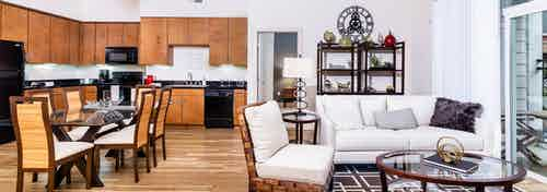 Interior view of a living room and kitchen at AMLI Park Avenue apartments with a dining room table and a plush white couch