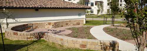 Paw park at AMLI on Riverside with a paved walking path and green grass with short brick ledges and a small dog walking