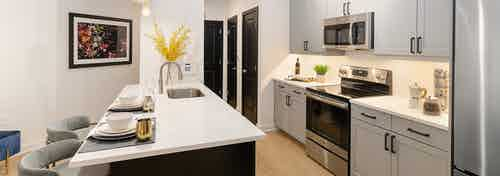 Kitchen at AMLI Quadrangle with white cabinets and countertops with stainless steel appliances and light wood flooring