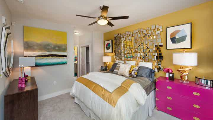 Interior of an AMLI Piedmont Heights bedroom with a gold wall while the others are grey with carpet and bright colorful decor