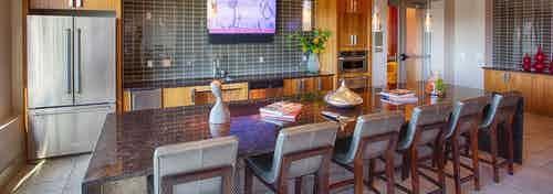 Resident kitchen at AMLI Denargo Market apartments with a long table and chairs and a tile back splash with a fridge and tv