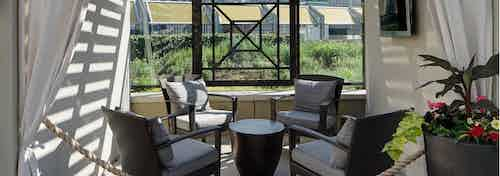 AMLI River North cabana view at dusk with four wicker chairs around a small table surrounded by flowing white curtains