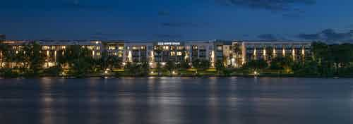 Nighttime exterior view of lit up AMLI South Shore building façade from across the river with palm trees and green trees