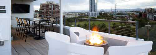 An exterior view of AMLI Riverfront Green roof top deck with fire pit and furniture and mountain view and sky scraper views