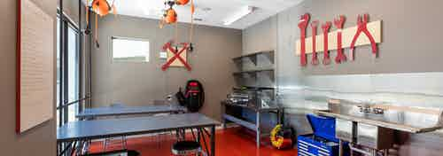 Makers space at AMLI on Aldrich with grey table and chairs and different stations with red tools on walls for creating
