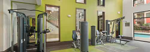 Interior of the fitness center at AMLI Ponce Park apartments with multiple weight machines and bright green two story wall