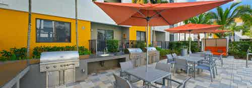 One of two barbeque areas at AMLI 8800 with electric grilling stations, outdoor tables with orange umbrellas and palm trees