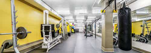 AMLI Bellevue Park fitness center with strength training equipment and free weights and squat rack and a hanging punching bag